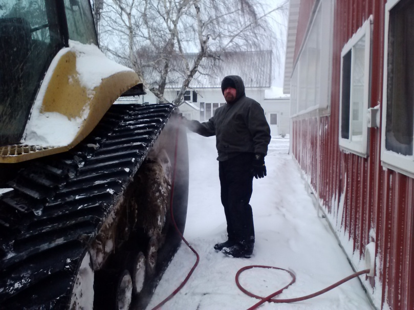 Dad unfreezing the tractor's tracks